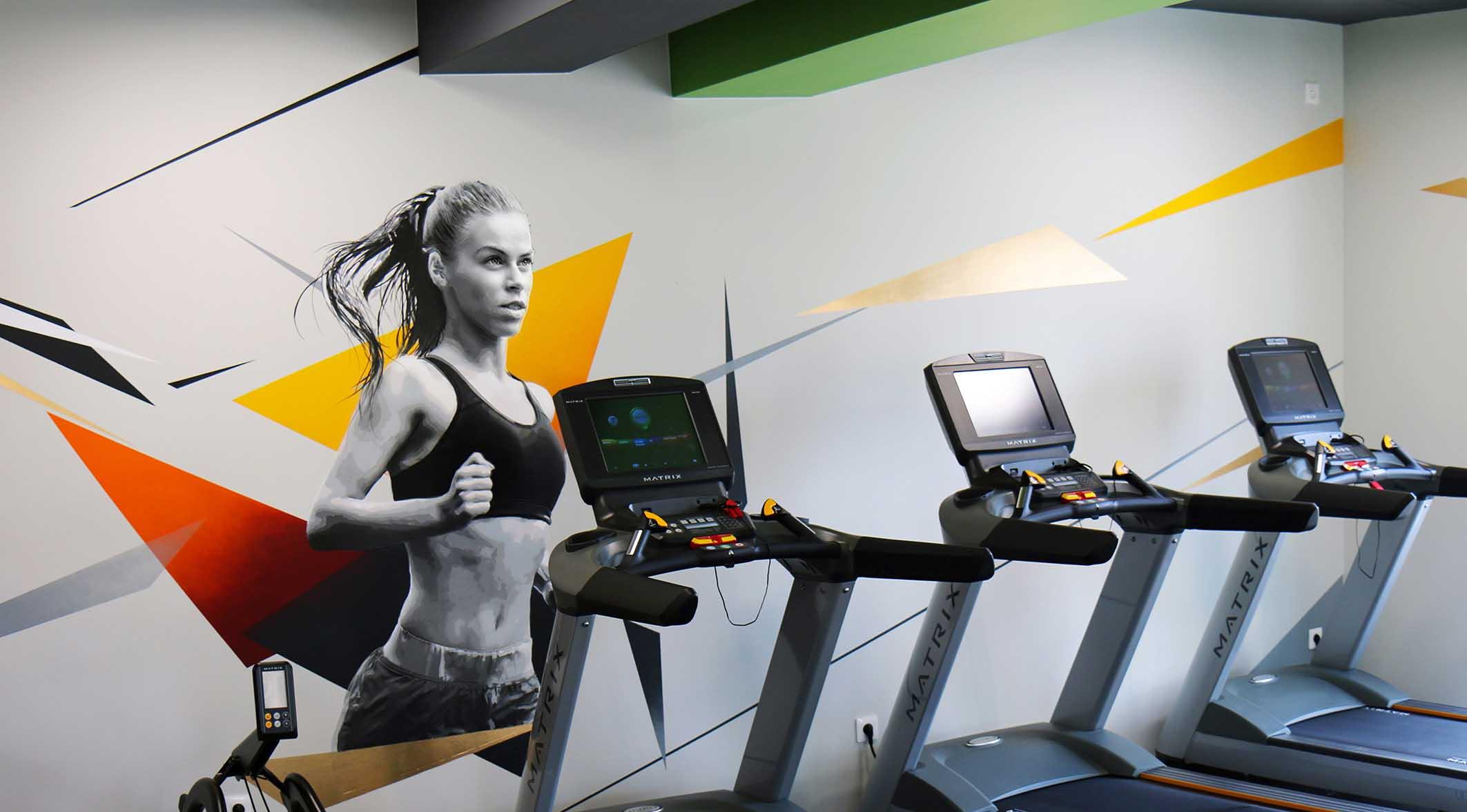 portrait d'une joggeuse et décorations colorées réalisés par frédéric michel-langlet dans la salle de sport fit & spa de la chapelle en serval